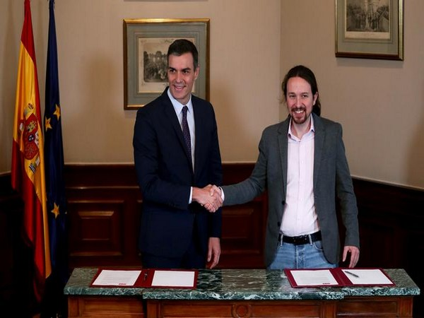 Spanish acting Prime Minister Pedro Sanchez and Unidas Podemos leader Pablo Iglesias shake hands during a news conference at Spain's Parliament in Madrid