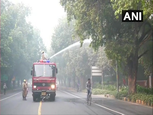 NDMC sprinkles water in the area around Feroz Shah Road to settle the dust, as a pollution control measure. [Photo/ANI]