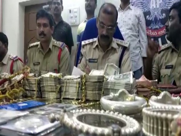 Andhra Pradesh police with the recovered cash and jewellery on Sunday.
