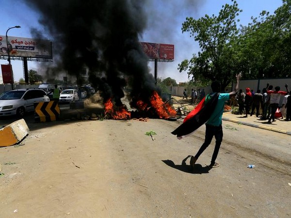 A Sudanese protester gestures as they burn tyres and barricade the road leading to al-Mek Nimir Bridge crossing over Blue Nile; that links Khartoum North and Khartoum, in Sudan on Monday