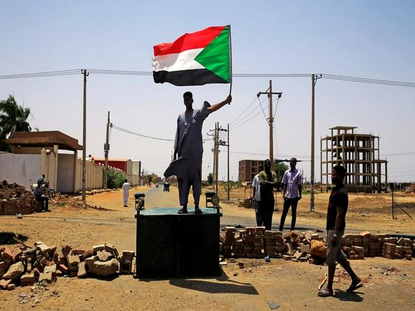 A protester holds up the flag of Sudan (Photo/Reuters)