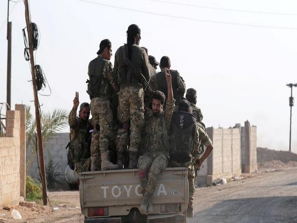 Turkey-backed Syrian rebel fighters enter the village of Yabisa, near the Turkish-Syrian border.