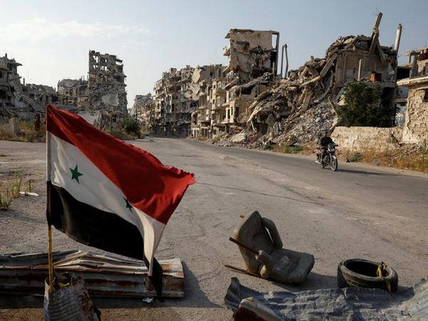 A Syrian flag amidst the devastation caused by the Syrian war (Photo/Reuters)