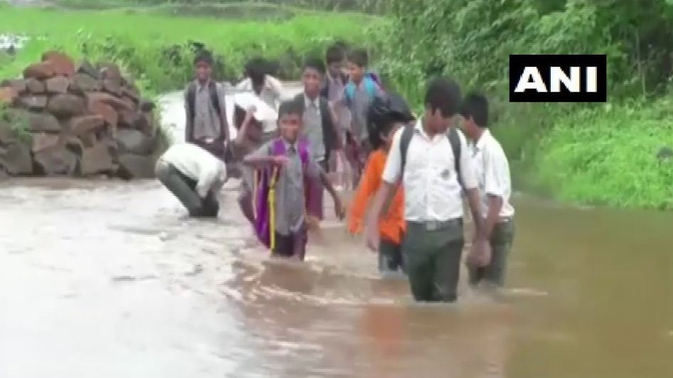 Students crossing the 3-foot-deep flooded road to reach school in Thane in Maharashtra. Photo/ANI