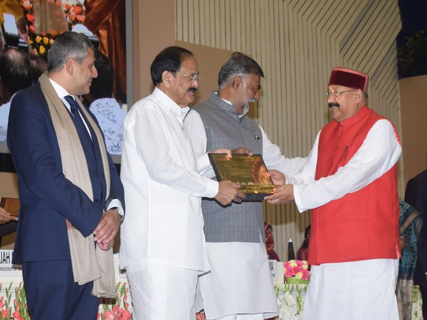 Vice President Venkaiah Naidu awarding Uttarakhand's tourism minister Satpal Maharaj at the Vigyan Bhawan on Friday.