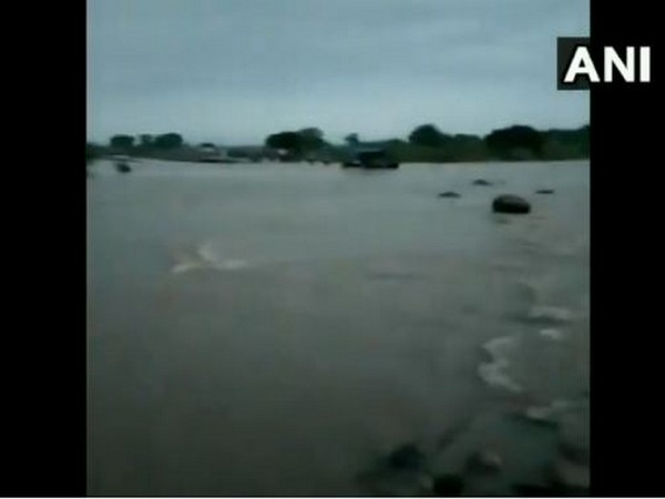 The tractor got swept away as it tried to cross the flooded bridge. Photo/ANI