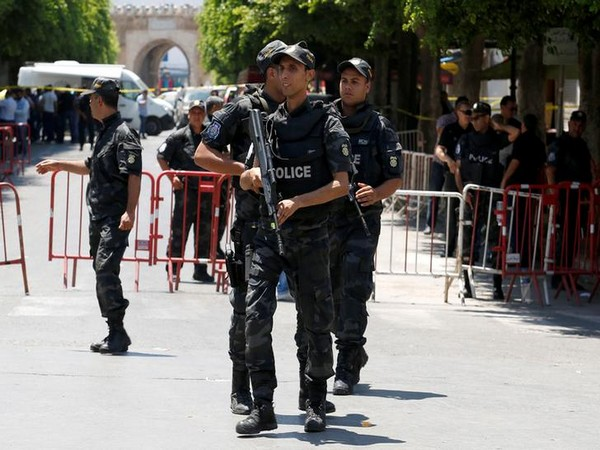 Police officers stand guard near the site of a suicide bombing attack in downtown Tunis on Thursday