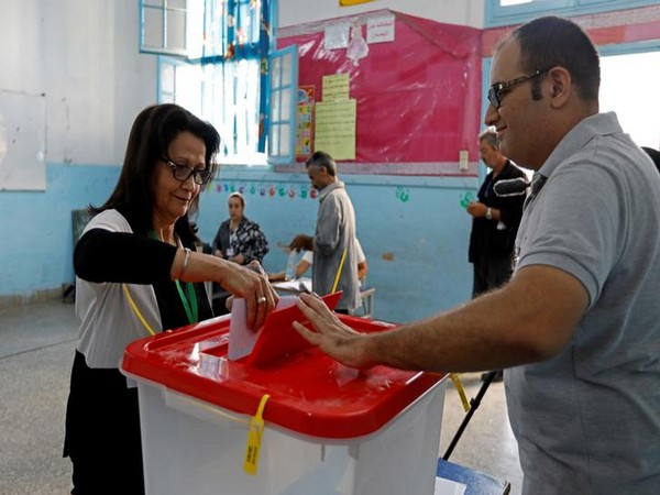 A woman casts her ballot at a polling station during parliamentary elections in Tunis