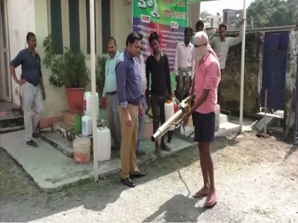 Delhi trainer (in purple shirt) giving traning to an official of Nainital state department on how to do fogging to control the spread of Dengue. [Photo/ANI]