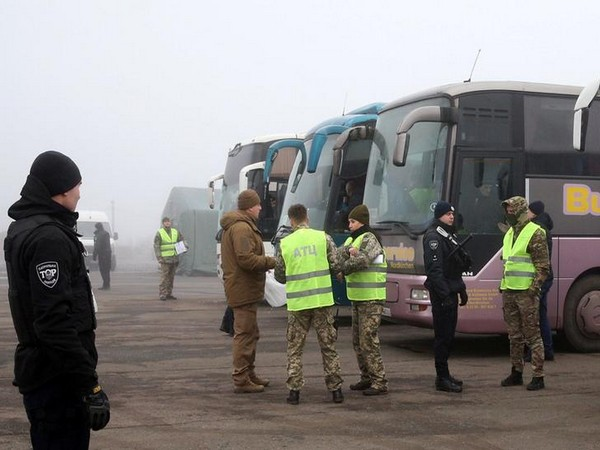 Ukrainian law enforcement officers stand guard near buses before exchange of prisoners in Ukraine on Sunday.