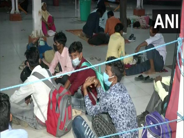 Migrant workers seen at Kaushambi bus stand on Monday.
