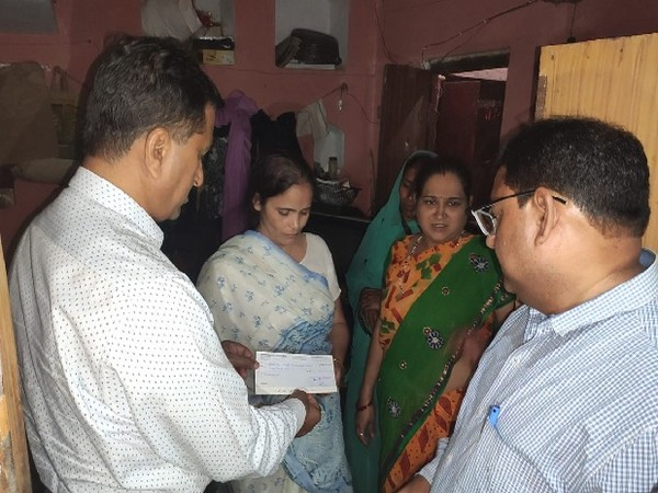 Officials handing over a cheque to Kamlesh Tiwari's wife in Sitapur, Uttar Pradesh on Wednesday.