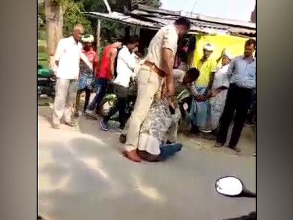 Visuals from the viral video in which two police personnel can be seen thrashing a man in Uttar Pradesh's Siddharthnagar district (Photo/ANI)