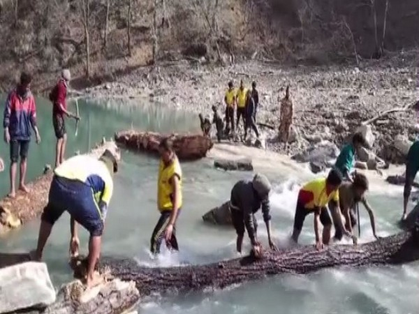 ITBP jawans with SDRF and other organisations removing tree trunks to widen