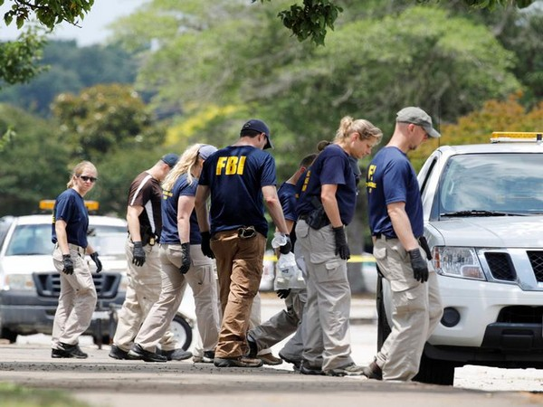 FBI members search a parking lot outside a municipal government building where a shooting incident occurred in Virginia Beach on Friday. (Photo courtesy:Reuters)