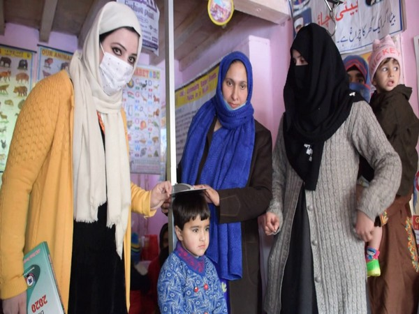 Anganwadi workers measuring child's height via stadiometer under ICDS scheme in Jammu and Kashmir's Pulwama on Wednesday. (Photo/ANI)