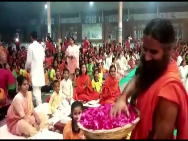 Ramdev celebrated Holi in Haridwar while throwing flower petals on those gathered at Patanjali Yogpeeth. (Photo/ANI)
