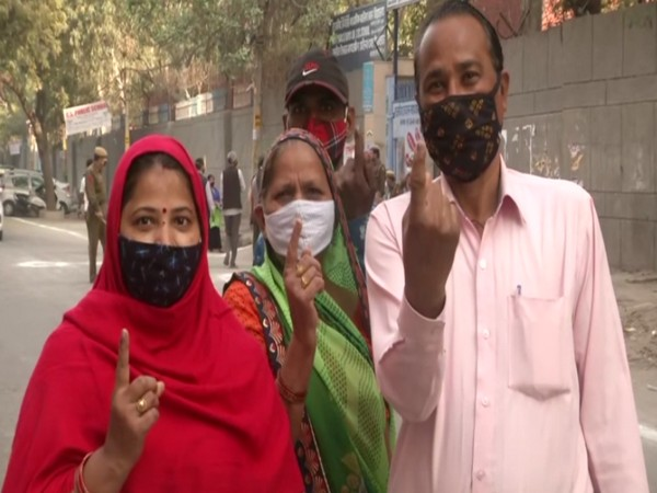 Voters outside a polling booth in Trilokpuri ward of Delhi. (Photo/ANI)