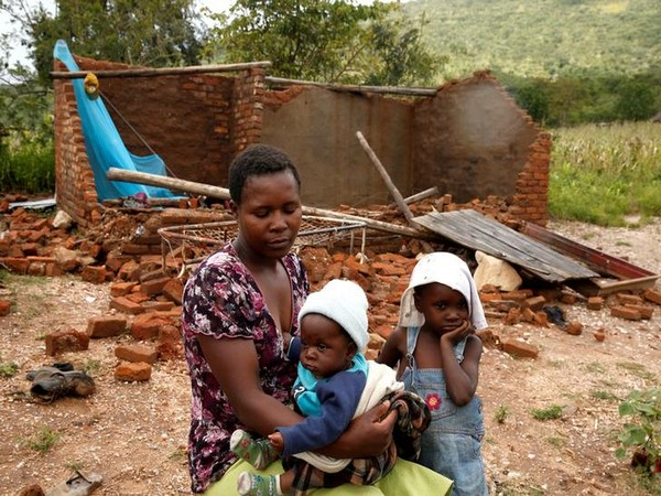 A family in front of their destroyed home following Cyclone Idai in Chimanimani district, Zimbabwe on March 18