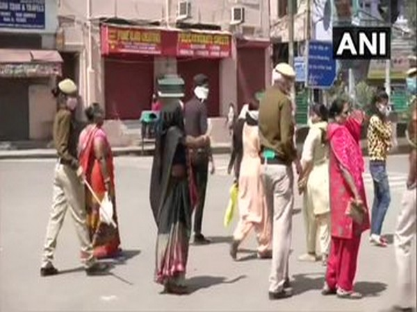 Police personnel disperse women outside a bank in Paharganj. Photo/ANI