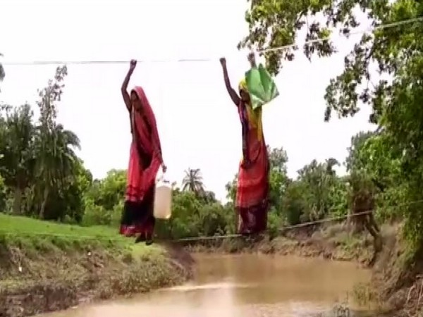 Women crossing the river stream through the make-shift rope bridge (Photo/ANI)