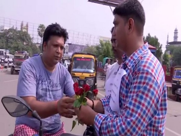 Krishna Kumar Singh distributed flowers to people who were driving without helmet or seat belt in Bihar's Patna on Saturday. Photo/ANI