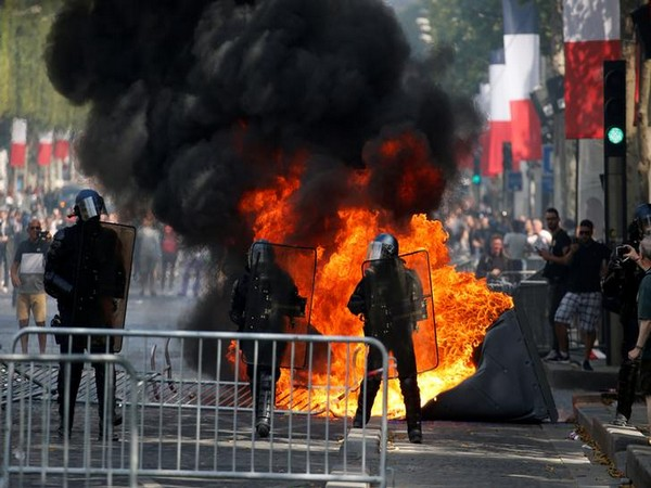 Law enforcement officials stand in front of a burning portable toilet at the Champs Elysees in Paris on Sunday (Photo/Reuters)