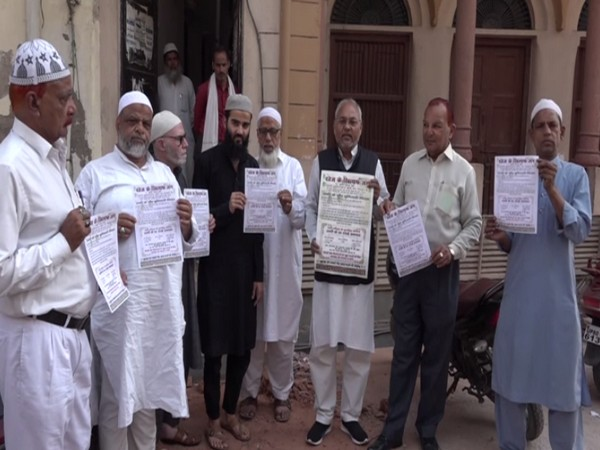 People of the community member display pamphlets in Agra. (Photo/ANI)